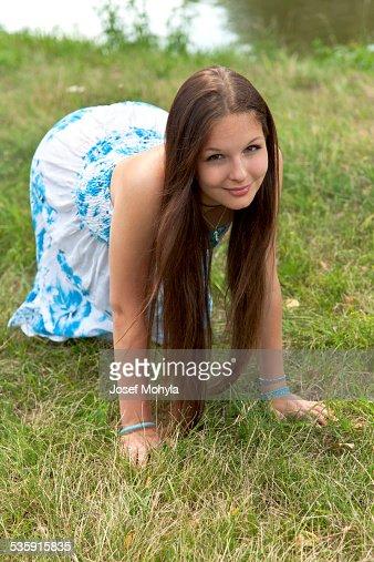 Mujer joven Arrodillarse en el césped por el río : Foto de stock