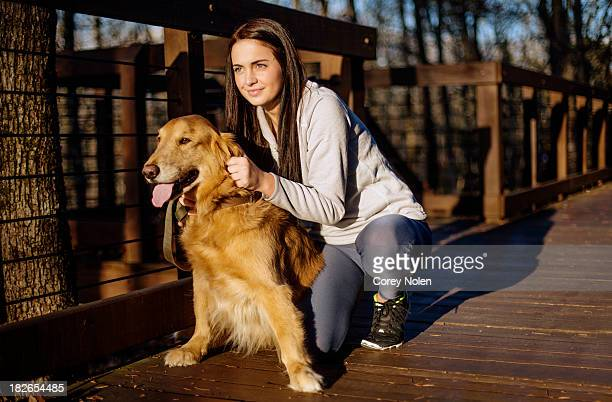 A young woman kneels down to pet her dog before a run.