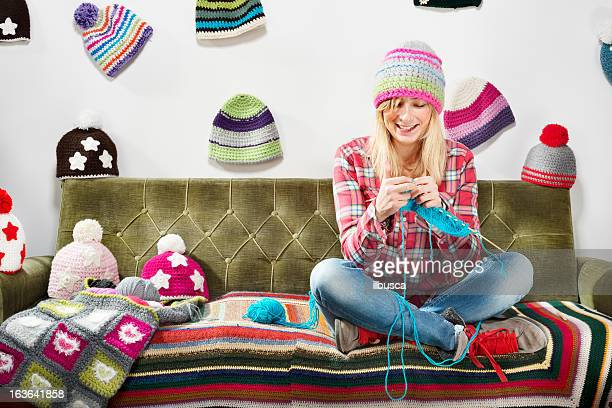 Young woman knitter portrait on couch with winter hats