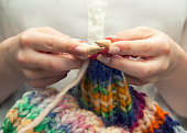 Young woman knitting a woolen colorful scarf. She is using bamboo knitting needles, size ten. Only her hands and arms are showing on the image. She has manicured nails. Neutral colored nailpolish. She