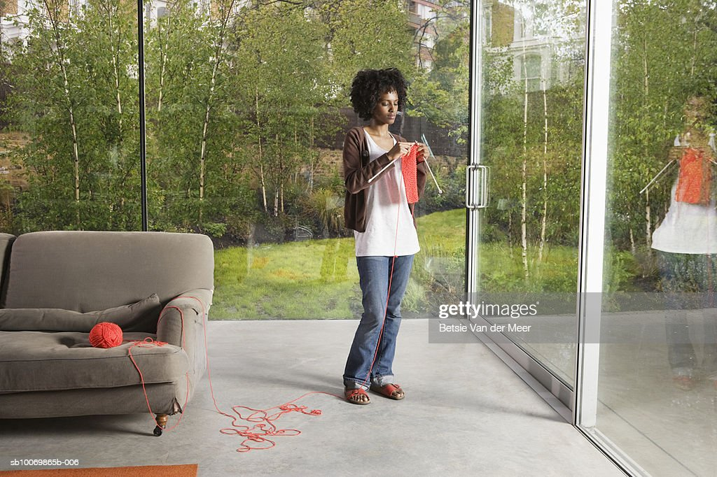 Young woman knitting in living room : Stock Photo