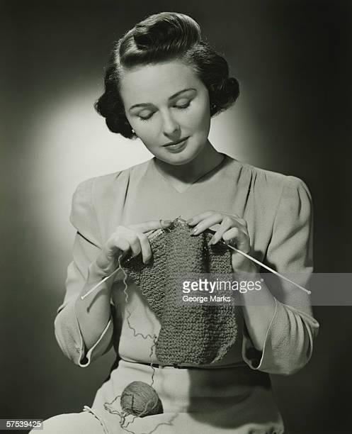 Young woman knitting in studio, (B&W)