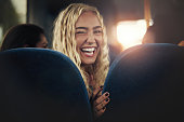 Laughing young blonde woman sitting alone on a bus looking over her shoulder and winking