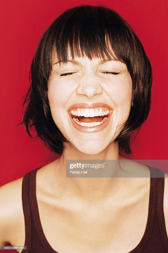 Young woman laughing, eyes closed, close-up : Stock Photo