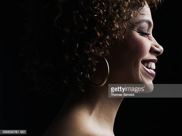 Young woman laughing, eyes closed, side view