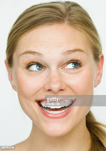 Young woman laughing, looking to side