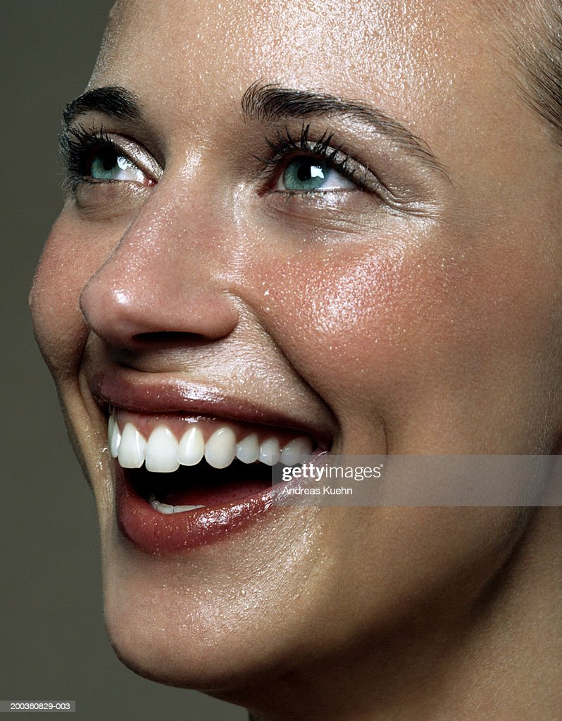 Young woman laughing, looking upwards, close-up