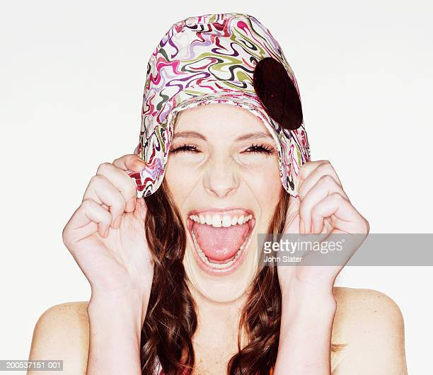 Young woman laughing, pulling dwon hat, close-up, portrait