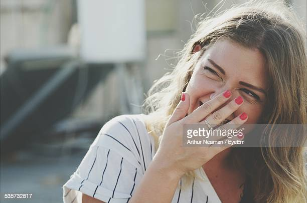 Young Woman Laughing While Hiding Mouth With Hand