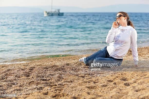 Junge Frau lacht während Sie mit Handy am Strand