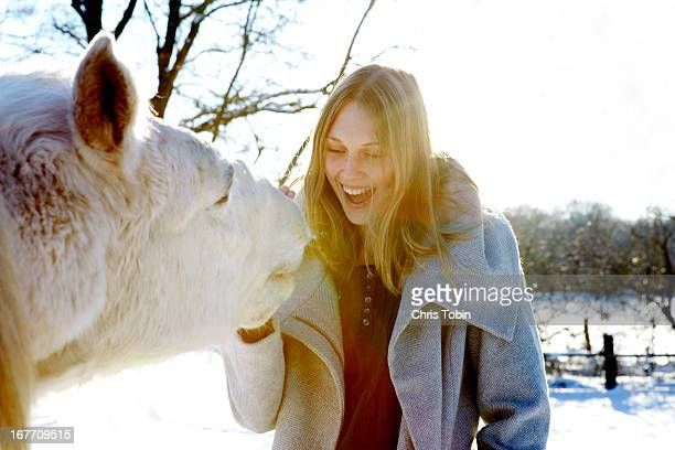 Young woman laughing with her horse
