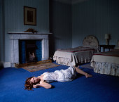 Young woman laying on floor in bedroom