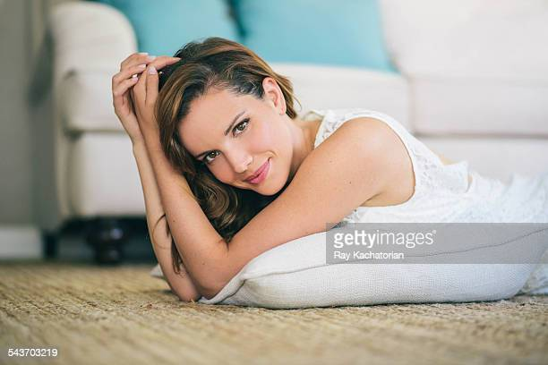 Young woman laying on floor smiling