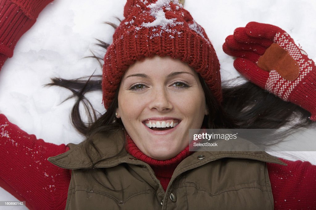Young woman laying on snow smiling : Stock Photo