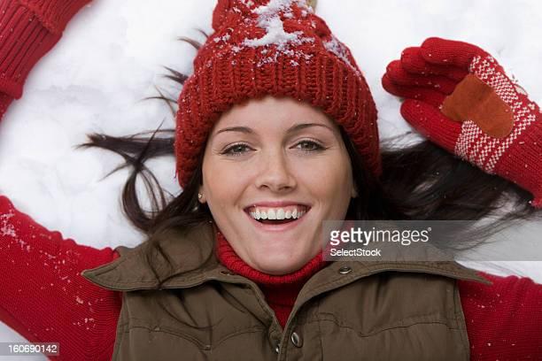 Jeune femme soulevant sur la neige souriant