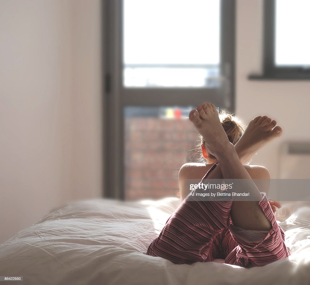 Young woman laying on the bed in the sunshine : Stock Photo