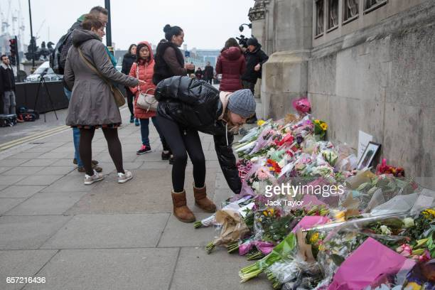 A young woman lays flowers outside the Houses of Parliament following Wednesday's attack on Westminster on March 24 2017 in London England A fourth...