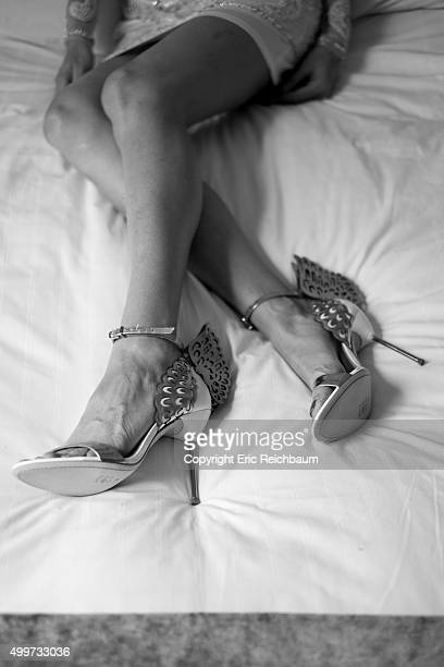 A young woman lays on a bed in dress shoes