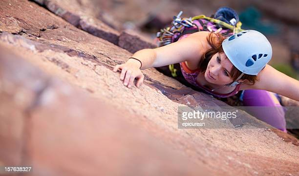 Young woman leading a climbing route in Colorado