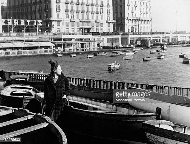 A young woman leaning against a boat and watching Borgo Santa Lucia with the famous restaurants by the sea Naples 1963