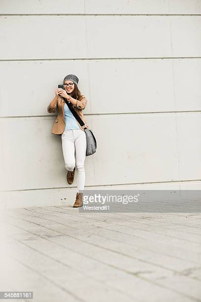 Young woman leaning against a wall taking a selfie with her smartphone