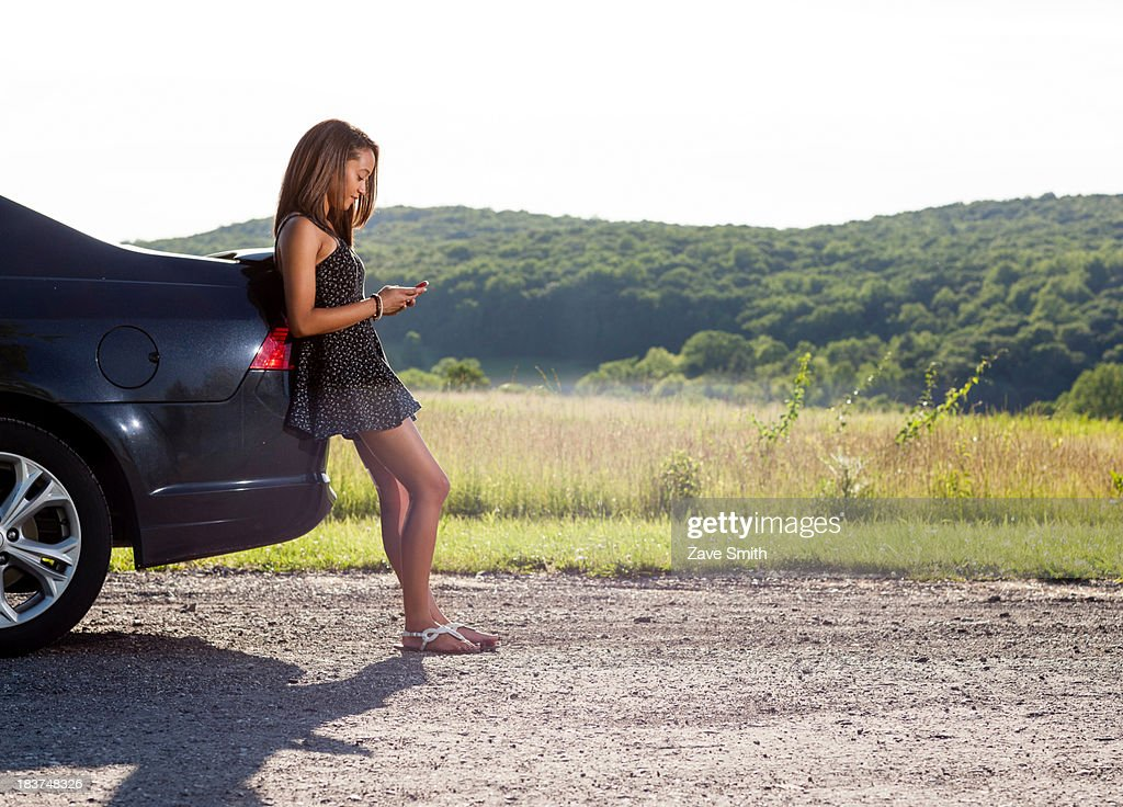 Young woman leaning against car using cell phone : Stock Photo