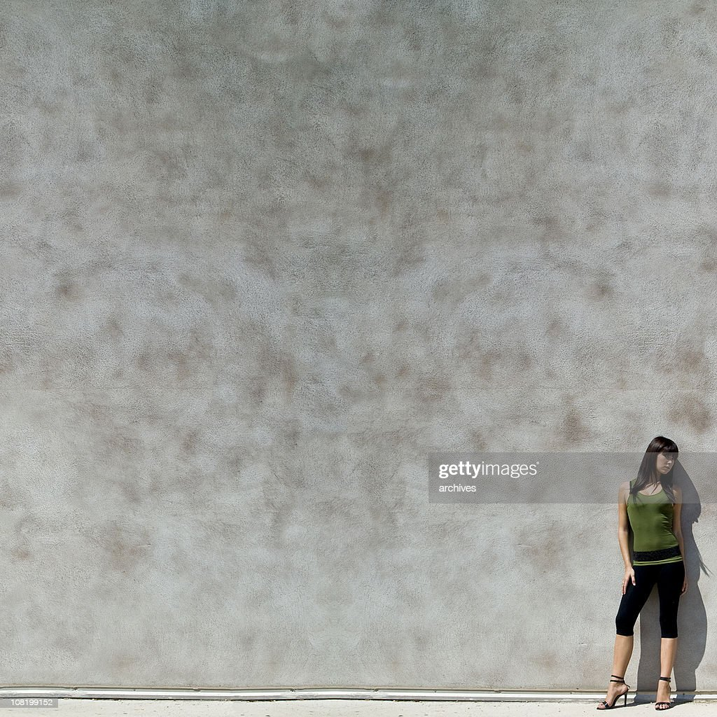 Young Woman Leaning Against Concrete Wall with Large Copy Space : Stock Photo