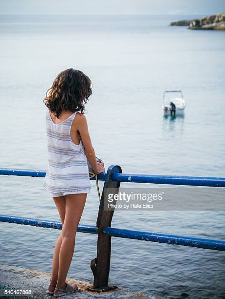Young woman leaning against fence in front of beach bay
