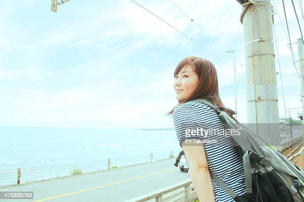 Young woman leaning against fence, looking out to sea