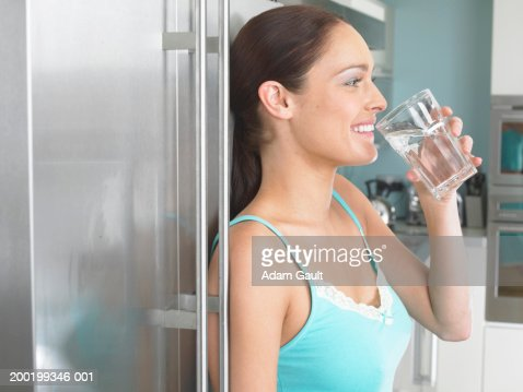 Young woman leaning against fridge, drinking glass of water, side view : Stock Photo