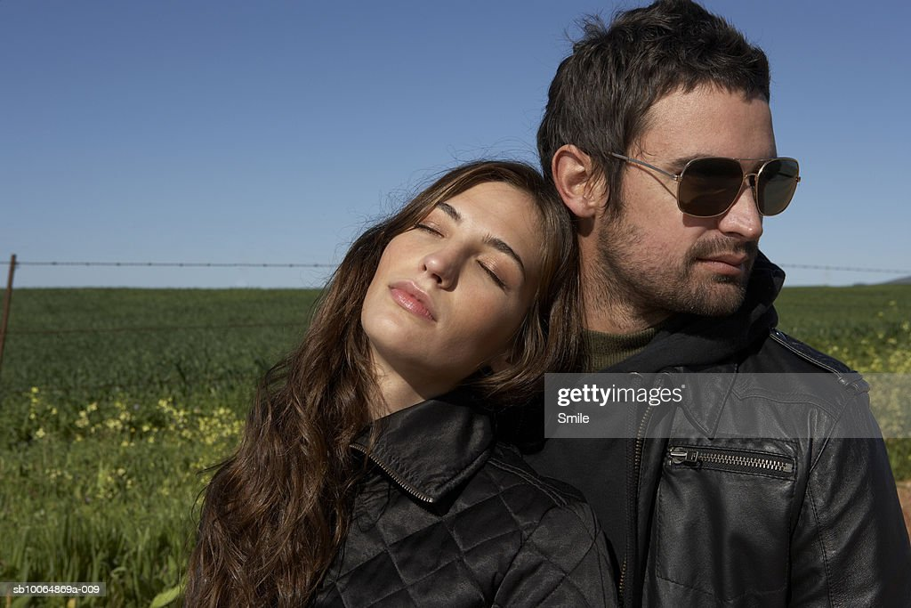 Young woman leaning against man with eyes closed : Stock Photo