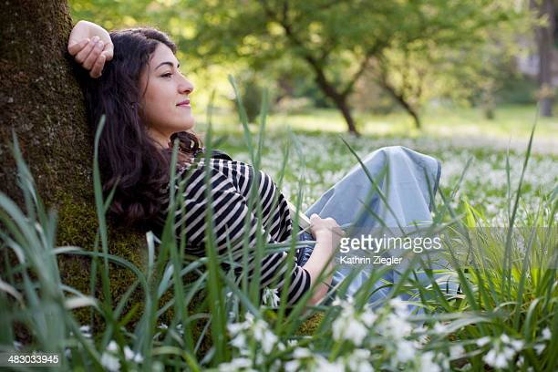 young woman leaning against tree, relaxing