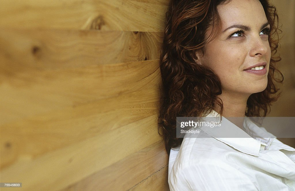 Young woman leaning against wall,smiling,head and shoulders : Stock Photo