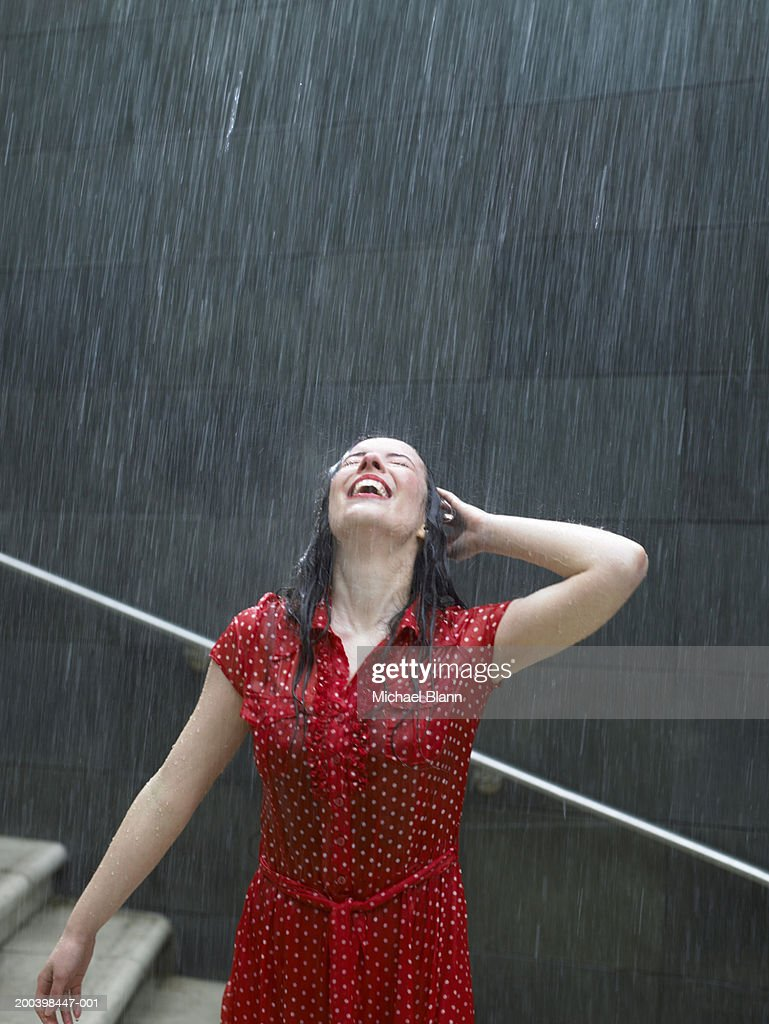 Young woman leaning back on steps in rain, hand behind head
