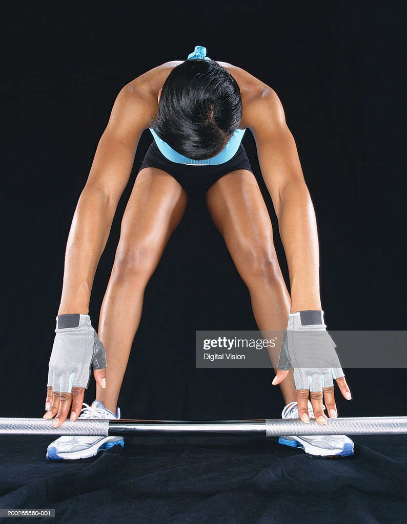 Young woman leaning down to pick up barbell : Stock Photo