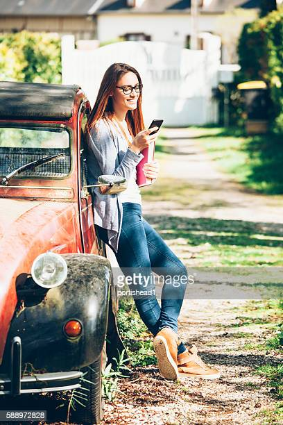 Young woman leaning on a car and using smart phone