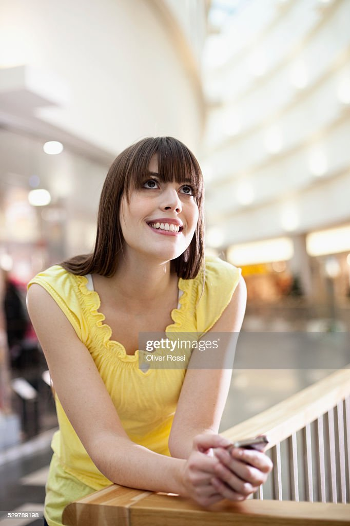 Young woman leaning on a railing : Stock-Foto