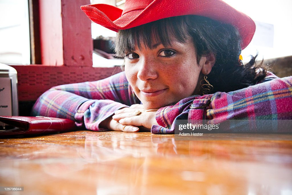 A young woman leaning on a table in a bar. : Stock Photo