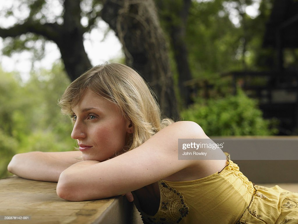 Young woman leaning on balcony, resting chin on arms, close-up : Stock Photo