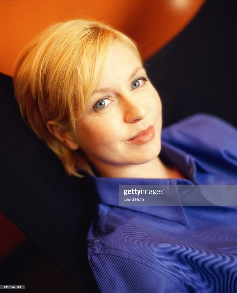 Young woman leaning on chair, portrait, elevated view : Stock Photo