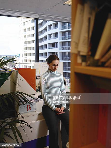 Young woman leaning on desk in office
