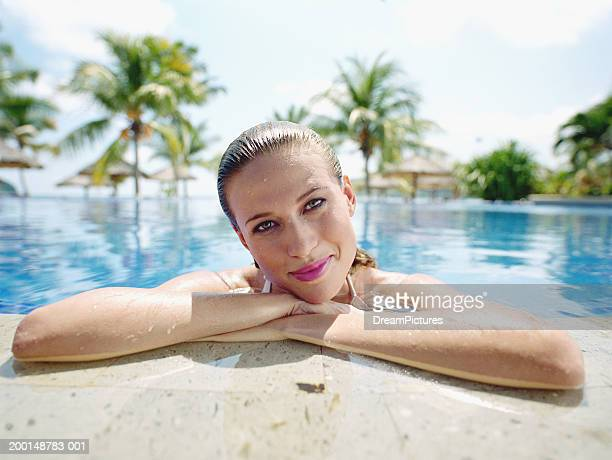 Young woman leaning on edge of swimming pool, portrait