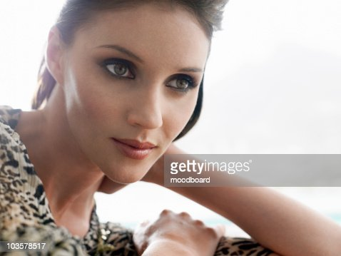 Young woman leaning on elbow indoors, close-up : Stock Photo