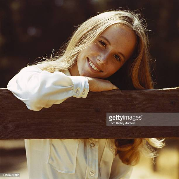 Young woman leaning on fence, smiling, portrait, close-up