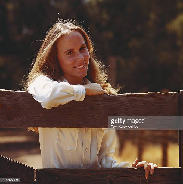 Young woman leaning on fence, smiling, portrait