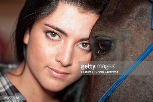 Young woman leaning on horse, close up : Stock Photo