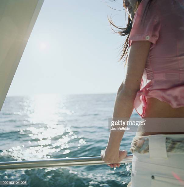 Young woman leaning on railing of yacht, rear view (mid section)