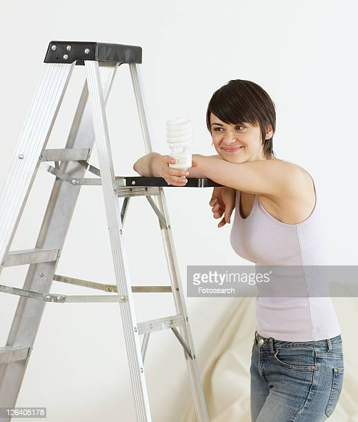 Young Woman Leaning on Stepladder and Holding Light bulb