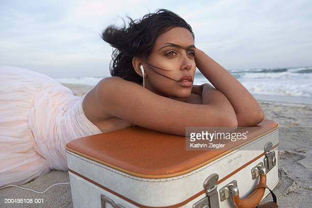Young woman leaning on suitcase, wearing earphones on beach