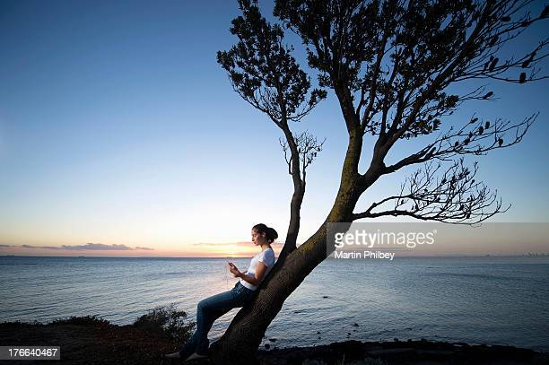 Young woman leaning on tree at dusk